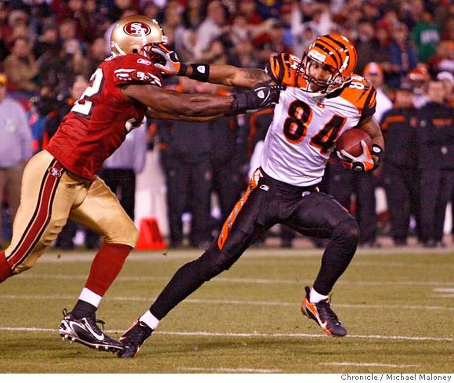 Cincinnati Bengals T.J. Houshmandzadeh (84) gives San Francisco 49ers Michael Lewis (32) a straight arm to avoid a tackle.  The San Francisco 49ers host the Cincinnati Bengals in a NFL football game at Monster Park in San Francisco, CA on Saturday, 12-15-07. 49ers won 20-13.  Photo by Michael Maloney / San Francisco Chronicle Photo: Michael Maloney
