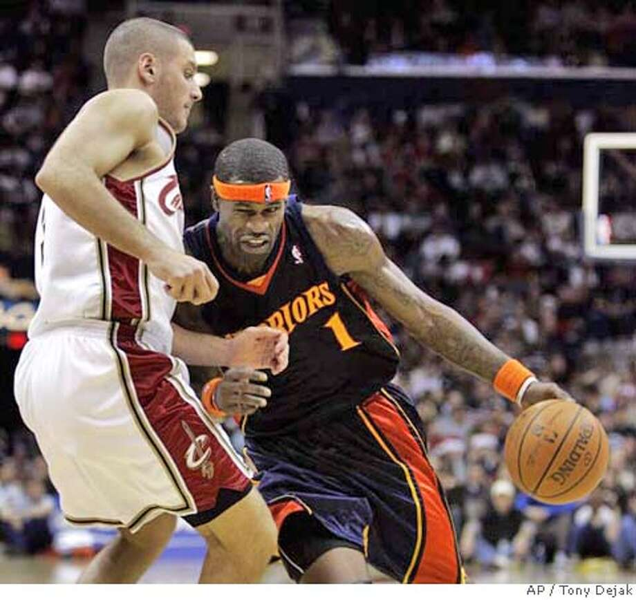 Golden State Warriors' Stephen Jackson, right, drives to the basket against Cleveland Cavaliers' Sasha Pavlovic, from Serbia, in the third quarter of an NBA basketball game, Sunday, Dec. 23, 2007, in Cleveland. The Warriors won 105-96. (AP Photo/Tony Dejak) Photo: Tony Dejak
