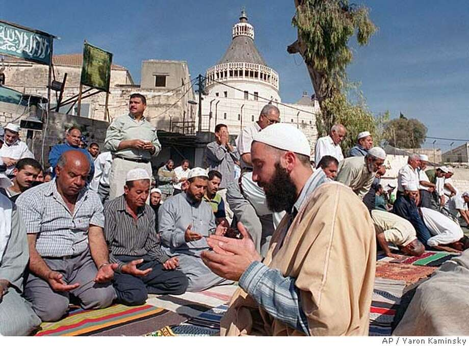 Muslim worshipers pray at the site of a proposed mosque outside the Basilica of the Annunciation, background, in Nazareth, the town of Jesus' boyhood Monday, Nov. 22, 1999. Israel will protect Christian interests in Nazareth, town of Jesus' boyhood, even as Muslims plan to build a mosque near the Christian holy site there, an Israeli official said Sunday. Public Security Minister Shlomo Ben-Ami sought to ease tensions before Tuesday's planned laying of a cornerstone for the mosque in a plot of land neighboring the basilica, where tradition says an angel told Mary she would give birth to Jesus. (AP Photo/Yaron Kaminsky) CAT Photo: YARON KAMINSKY