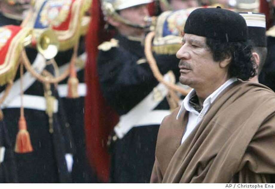 Libyan leader Col. Moammar Gadhafi reviews the French Republican Guard upon his arrival at the Elysee Palace for a meeting with French President Nicolas Sarkozy, in Paris, Monday, Dec. 10, 2007. Gadhafi takes a giant stride toward international respectability Monday, making a visit to France likely to conclude with deals worth millions, but drawing protests, including from a government minister. (AP Photo/Christophe Ena) Photo: CHRISTOPHE ENA