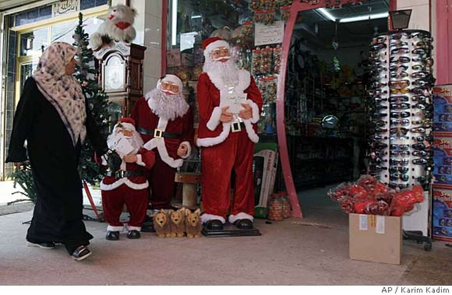 An Iraqi woman walks past Christmas decorations displayed in front of a store on Palestine Street in central Baghdad, Iraq, on Friday, Dec. 14, 2007. (AP Photo/Karim Kadim ) Photo: Karim Kadim