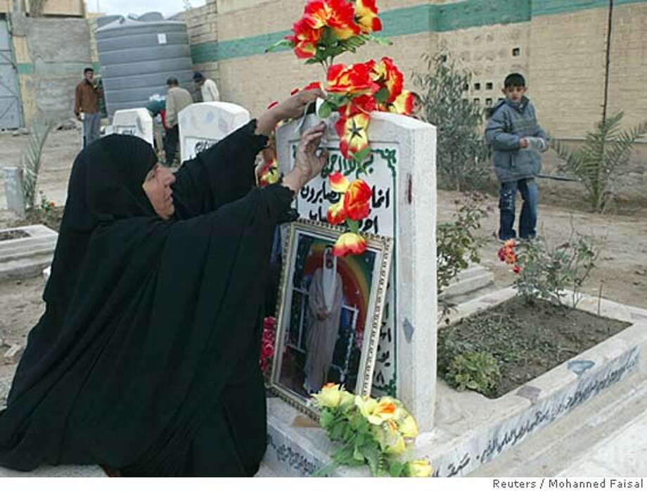 A woman attaches flowers on the grave of a relative in a cemetery on the first day of the Muslim festival of Eid-al-Adha in Falluja, 50 km (30 miles) west of Baghdad, December 19, 2007 REUTERS/Mohanned Faisal (IRAQ) 0 Photo: MOHANNED FAISAL