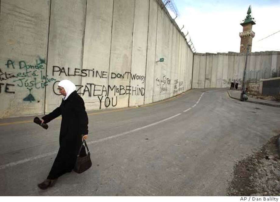 A Palestinian woman walks next to a section of Israel's separation barrier in the West Bank village of Abu Dis, on the outskirts of Jerusalem, Monday, Dec. 17, 2007. The world rallied to the support of the embattled Palestinian government Monday, pledging $7.4 billion in aid over the next three years at a donors' conference, a sum that tops the Palestinians' own expectations. World leaders at the conference also urged Israel to ease restrictions on movement in the West Bank and Gaza to make a recovery of the Palestinian economy possible. (AP Photo/Dan Balilty) Photo: DAN BALILTY
