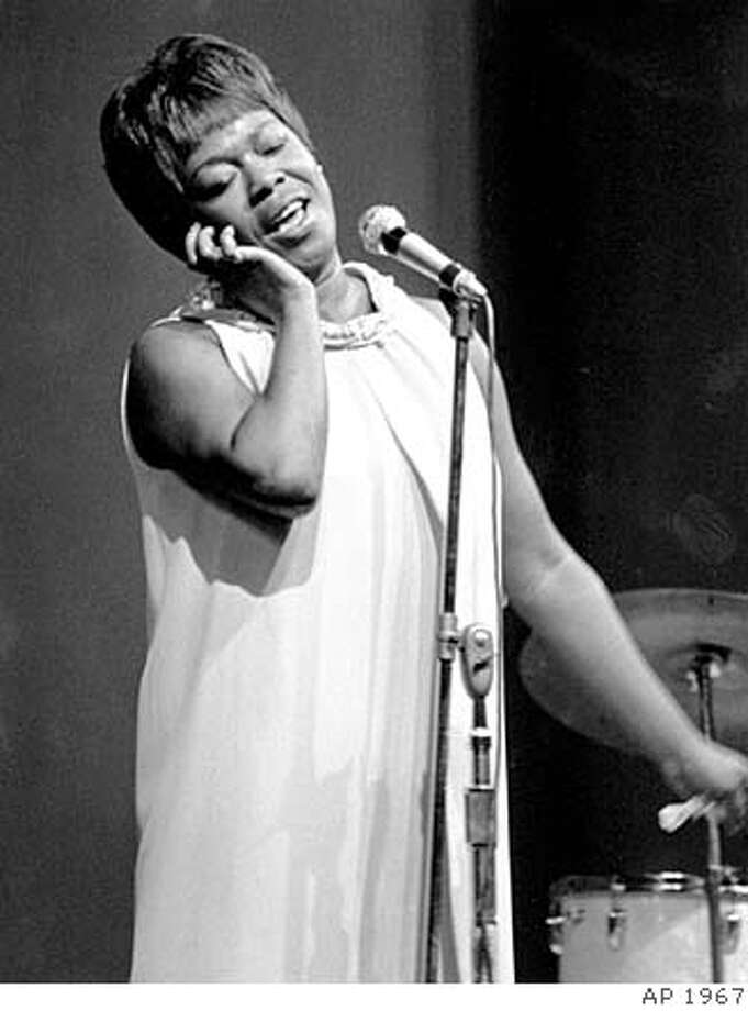 "ADVANCE FOR WEEKEND EDITIONS, JUNE 21-24--FILE--Vocalist Sarah Vaughan sings at the Newport Jazz Festival's closing night in Newport, R.I., in this July 3, 1967, file photo. Jazz singer Dianne Reeves's newest album ""The Calling,"" her ninth for the Blue Note label and 11th overall, is a heartfelt tribute to Vaughan. Like Vaughan, who recorded her albums live in the studio, Reeves did nearly all of her album in a Burbank, Calif., studio with an orchestra plus a jazz ensemble, including such guest soloists as pianist Mulgrew Miller, saxophonist Steve Wilson, and guitarists Russell Malone and Brazil's Romero Lubambo. (AP Photo/FILE)  Ran on: 09-16-2007  The 1958 set by Louis Armstrong, top, is the first CD to be issued from Monterey Jazz Festival archives. Miles Davis, center, was recorded in 1963 and Dizzy Gillespie, right, in '65.  Ran on: 12-16-2007 Photo: AP"