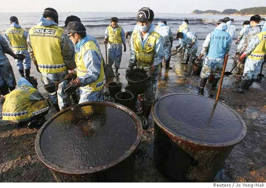 Volunteers from the police make efforts to remove crude oil spilt over Mallipo swimming beach after a Hong Kong-registered oil tanker accident, in Taean, about 170km (106 miles) southwest of Seoul, December 9, 2007. South Korea deployed over 100 ships and thousands of troops on Sunday to clean up the worst oil spill in its history, which has blackened beaches, coated birds in tar and cast a foul smell over a nature reserve. REUTERS/Jo Yong-Hak (SOUTH KOREA) 0 Photo: JO YONG-HAK