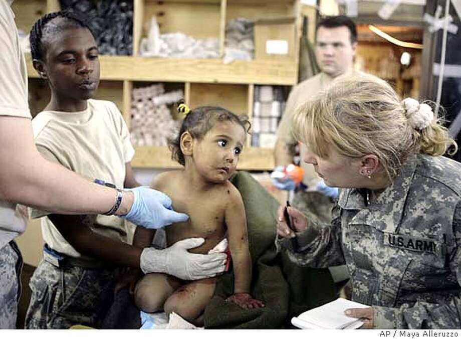 An injured Iraqi child is calmed by an interpreter, right, as she is treated by medics from 1st Battalion, 30th Infantry Regiment at Patrol Base Murray, near Baghdad, after a mortar strike injured two girls in the town of Arab Jabour, south of Baghdad, Iraq, Tuesday, Dec. 11, 2007. The girls were evacuated by helicopter to the 86th Combat Support Hospital in Baghdad. (AP Photo/Maya Alleruzzo) Photo: MAYA ALLERUZZO