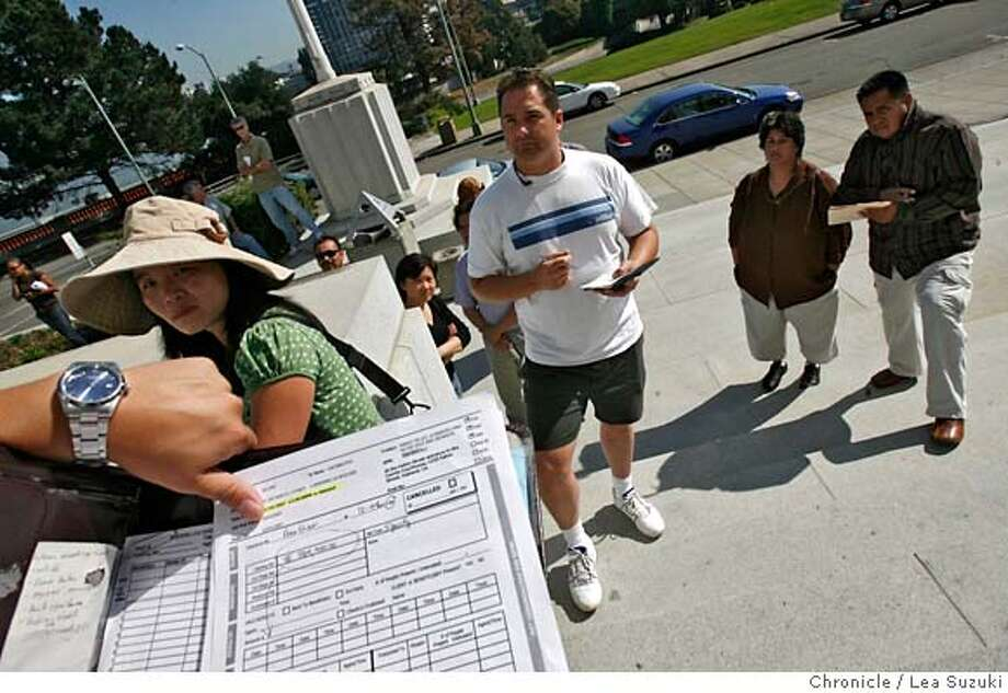 auctionxx_068_ls.jpg  SAVE FOR PROJECT. From right: Mario Tellez, Maria De La Vega, Chris Gray (in white T shirt with blue stripe) and Jared Thao, Trustee Agent for FIS (Fidelity National Information Services who has only his hands showing). Thao conducts the auction in front of the Alameda County Courthouse while Tellez and De La Vega watch and listen. Mario Tellez and his wife Maria De La Vega attend the scheduled foreclosure auction of their Livermore duplex on the Alameda County Courthouse steps on Wednesday. Lea Suzuki / The Chronicle Photo taken on 10/24/07 in Oakland, CA, USA. �2007, San Francisco Chronicle  MANDATORY CREDIT FOR PHOTOG AND SAN FRANCISCO CHRONICLE/NO SALES-MAGS OUT Photo: Lea Suzuki