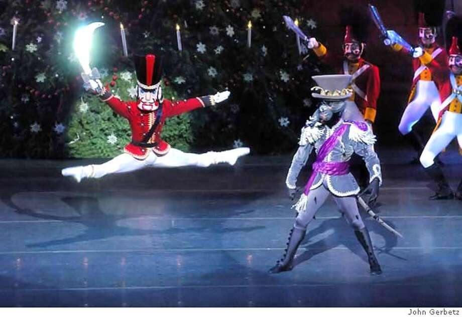 """The Nutcracker flashes his sword at the terrible Mouse King, in Act I, scene 3 """"A Curious Combat"""" from Dennis Nahat's stunning version of THE NUTCRACKER, presented by Ballet San Jose, December 13-23, 2007. Photo by John Gerbetz Photo: Ho"""