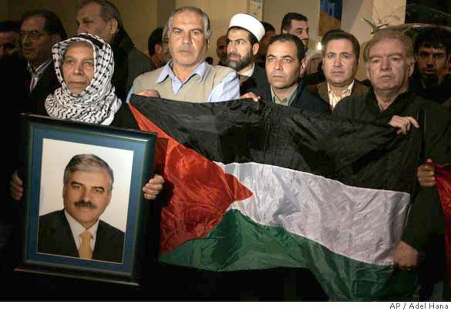 Palestinian supporters of Omar Al-Ghoul, an advisor to Palestinian Authority Prime Minister Salam Fayyad protest against his detention by Hamas forces in Gaza City, Friday, Dec. 14, 2007. Armed gunmen burst into the home of the top Fatah official in Gaza early Friday and kidnapped him, the man's family said, in the first such abduction of a politician since Hamas forces routed their Fatah rivals and overtook the strip in June. (AP Photo/Adel Hana) Photo: ADEL HANA