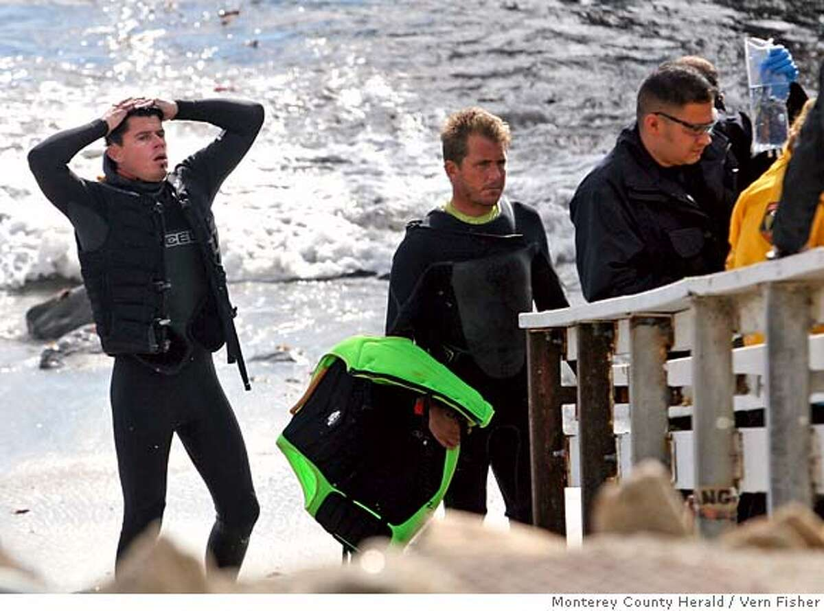 Homer Henard and Adam Replogle, both from Santa Cruz, Calif., look on as CPR is performed on Peter Davi, who drowned while surfing in Pebble Beach, Calif., Tuesday, Dec. 4, 2007. Davi, a big wave surfer from Monterey County, Calif., died in the unforgiving waves of Ghost Trees, a Monterey County surf spot known for its 20-foot waves. Witnesses say 45-year-old Davi lost his board and was attempting to swim to shore, but never made it. Friends of Davi lost sight of him and later found him floating in the water unconscious. (AP Photo/Monterey County Herald, Vern Fisher)