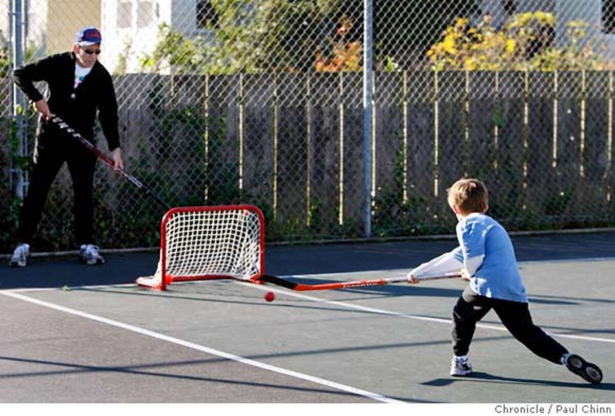 Liam Sherry, 6, hones his street hockey skills with his dad Bob (left) before supporters of the Proposition A bond measure kicked off the campaign at a rally at Cabrillo Playground in San Francisco, Calif. on Saturday, Dec. 8, 2007. Liam and Bob play hockey at the playground every weekend. PAUL CHINN/The Chronicle **Liam Sherry, Bob Sherry
