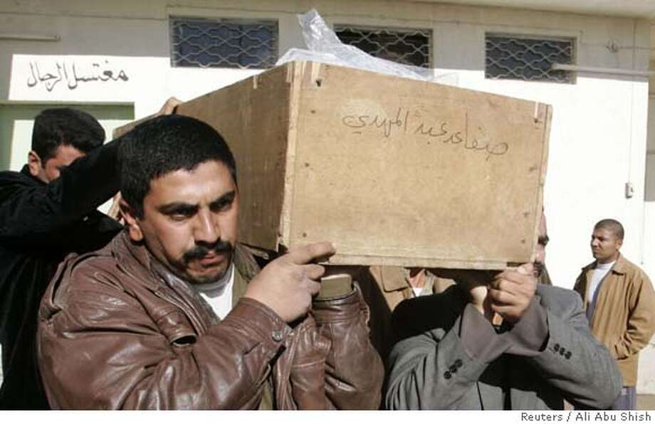 "Mourners carry a coffin of a victim, killed in Wednesday's bomb attack in Amara, during a funeral in Najaf, 160 km (100 miles) south of Baghdad December 13, 2007. Three car bombs ripped through a busy street in the Shi'ite city of Amara on Wednesday, killing 40 people and wounding 125 in one of the deadliest attacks in southern Iraq this year, police said. The inscription on the coffin reads""the coffin is a donation from late Safa Mahdi"". REUTER/Ali Abu Shish (IRAQ) 0 Photo: ALI ABU SHISH"