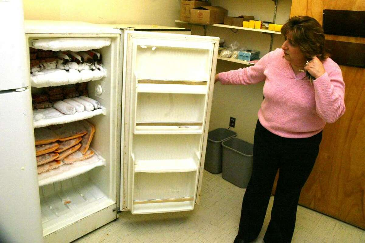 Jill Bruno, director of Bridgeport's Veterans Affairs office looks through a freezer at the Bridgeport veteran's food pantry in the Social Service and Health Department Building on East Main Street. There are 3 freezers but only one has any frozen meat, Monday, Nov. 2, 2009.