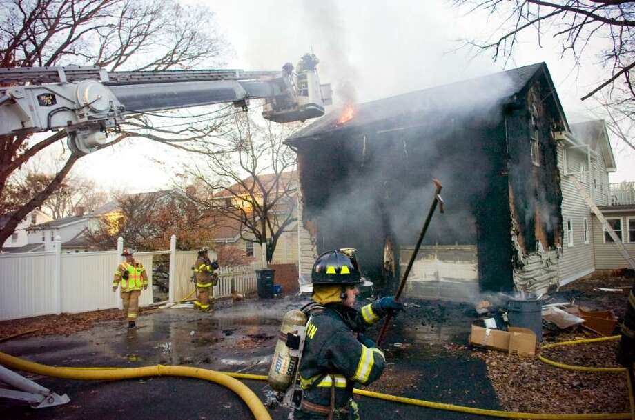 Firefighters battle a fire on Gilford St. in Stamford, Nov. 3, 2009. Photo: Chris Preovolos / Stamford Advocate
