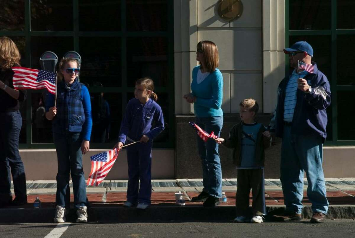 A family watches the annual Veteran's Day Parade in downtown Stamford, Conn. on Sunday, Nov. 11, 2009.