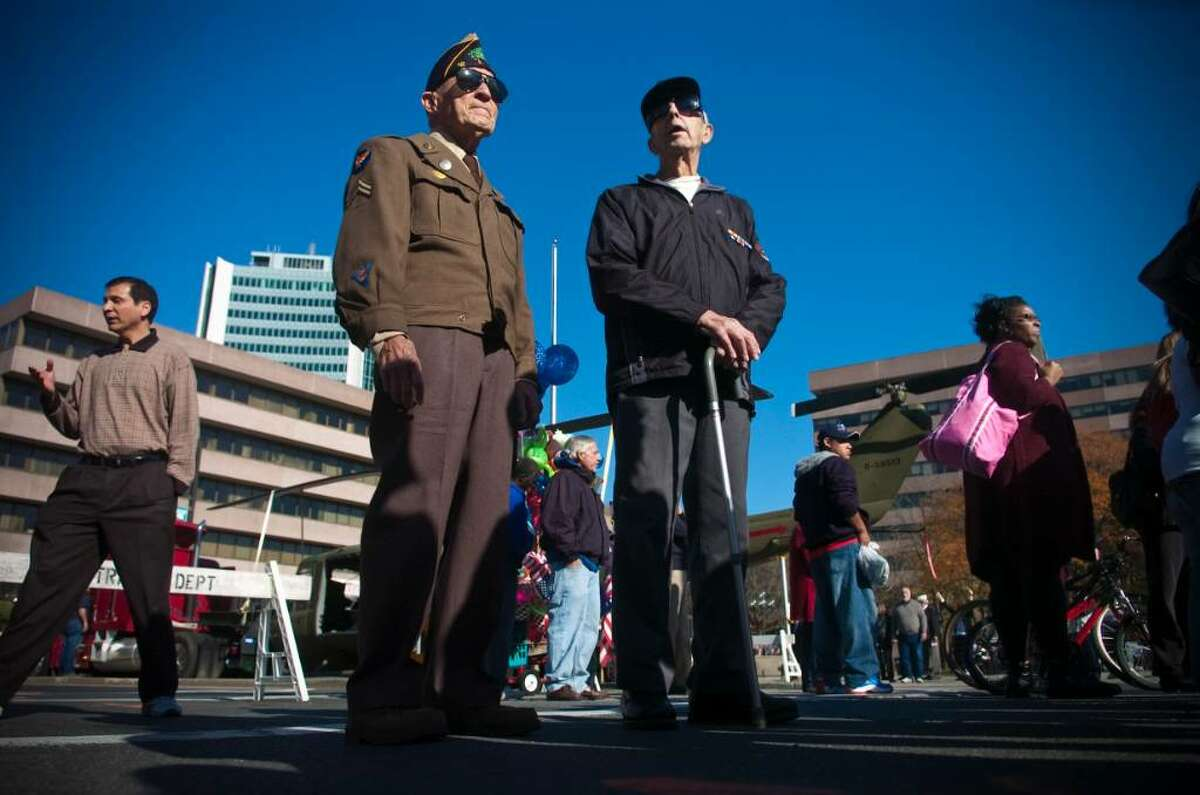 Veterans Nick Samodel, of Norwalk, left, and George Cartsounis, right, watch the annual Veteran's Day Parade in downtown Stamford, Conn. on Sunday, Nov. 11, 2009.