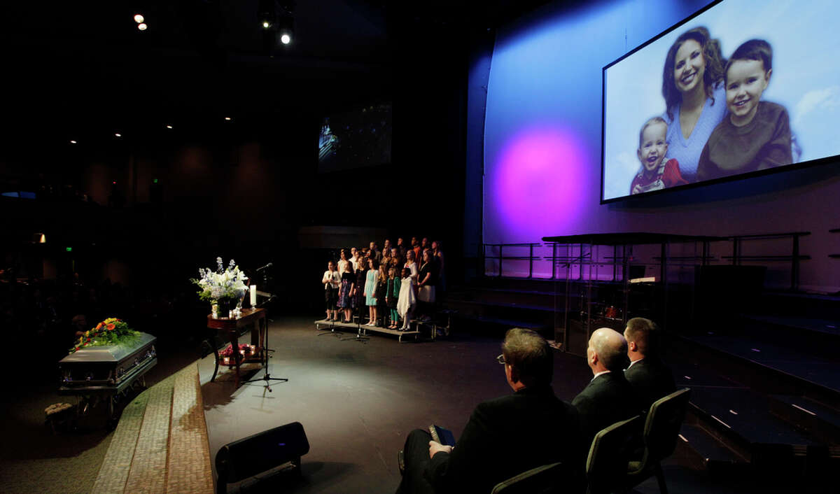 A photo of Susan Cox Powell and her sons Charlie, right, and Braden, left, is shown as a children's choir performs during a funeral service for Charlie and Braden Powell, Saturday, Feb. 11, 2012, in Tacoma, Wash. The boys died Feb. 5, 2012, when their father, Josh Powell, set fire to the home he was living in while they visited. Powell had been a person of interest in the 2009 disappearance of his wife Susan.