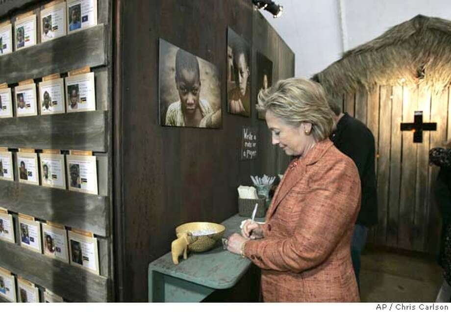 Democratic presidential hopeful, Sen. Hillary Rodham Clinton, D-N.Y., signs a note for the prayer wall in a AIDS exhibit at the Global Summit on AIDS & The Church at Saddleback Church in Lake Forest, Calif., Thursday, Nov. 29, 2007. (AP Photo/Chris Carlson) Photo: Chris Carlson