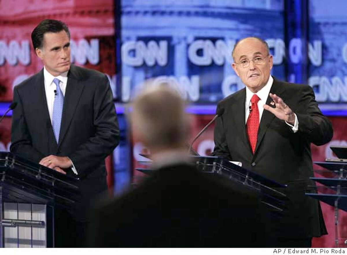 In this image provided by CNN, Republican presidential hopeful, former New York City Mayor Rudy Giuliani, right, speaks as Republican presidential hopeful, former Massachusetts Gov. Mitt Romney, listens, during the CNN/YouTube debate in St. Petersburg, Fla. Wednesday, Nov. 28, 2007. Debate moderator Anderson Cooper is in center foreground. (AP Photo/CNN, Edward M. Pio Roda) ** IMAGE PROVIDED BY CNN, NO SALES, TV OUT, NO ACCESS JAPAN ** IMAGE PROVIDED BY CNN, NO SALES, TV OUT, NO ACCESS JAPAN