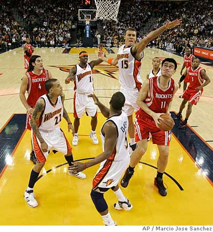 Houston Rockets center Yao Ming (11), of China,, right, tries to shoot as Golden State Warriors forward Andris Biedrins (15), of Latvia, defends during the first half of an NBA basketball game in Oakland, Calif., Thursday, Nov. 29, 2007. (AP Photo/Marcio Jose Sanchez) Photo: Marcio Jose Sanchez