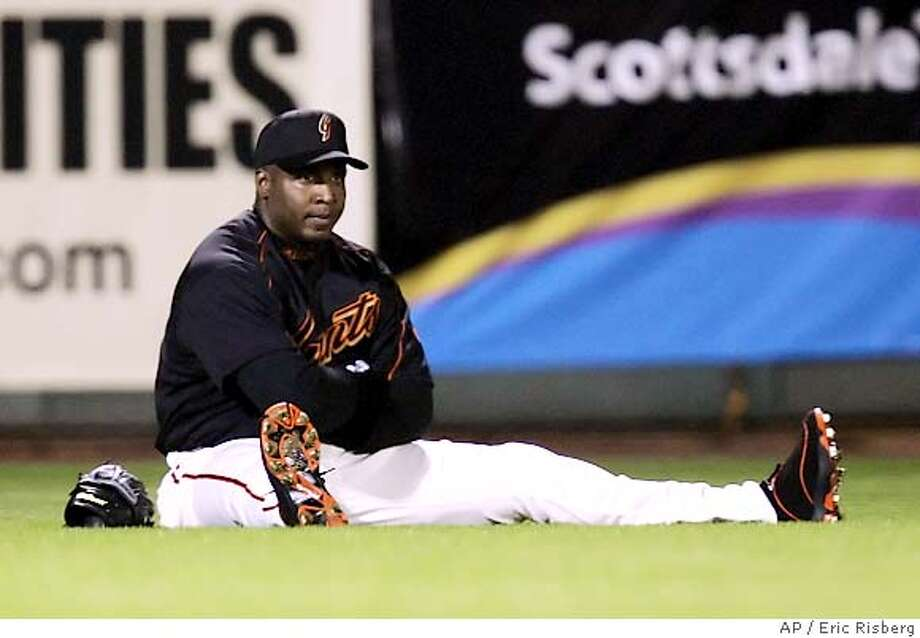 San Francisco Giants' left fielder Barry Bonds sits and rests on the grass during a pitching change in the fifth inning of their spring training night game against the Los Angeles Angels in Scottsdale, Ariz., Wednesday March 22, 2006.(AP Photo/Eric Risberg) Photo: ERIC RISBERG