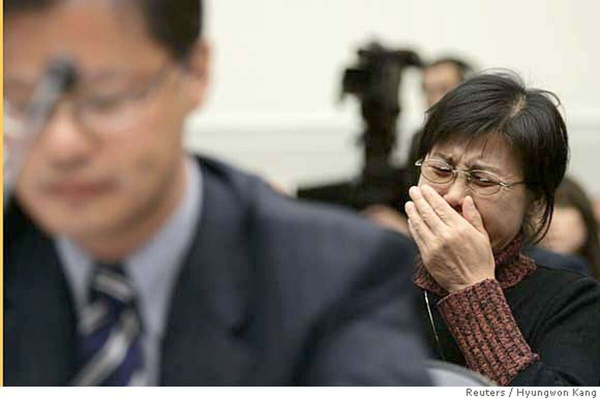 Gao Qin Sheng, mother of Shi Tao, a Chinese reporter who was sentenced last April to 10 years in prison for leaking state secrets abroad, cries as CEO of Yahoo! Inc. Jerry Yang (L) testifies before U.S. House Foreign Affairs Committee hearing on Capitol Hill in Washington November 6, 2007. The committee is hearing on