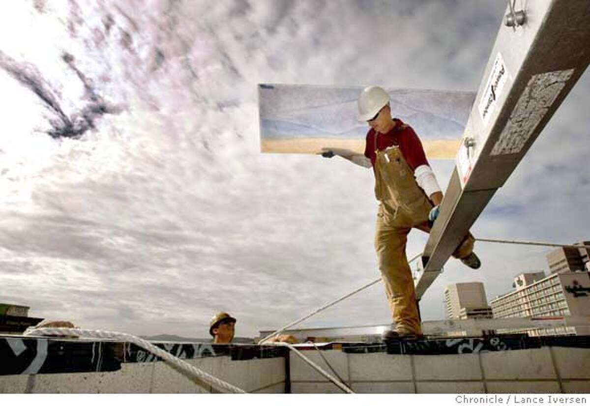 GLASS09_75987.JPG Glass Glaser Chris Del Fara carries one of several hundred-glass panels as he steps over a support beam during installation on a new San Francisco Condo Tower, SOMA Grand, at 1160 Mission Street. The art by Architectural glass artist Dorothy Lenehan spans three sides of the Tower. The project is said to be the biggest glass mural in San Francisco. OCTOBER 18th, 2007. Lance Iversen/The Chronicle (cq) SUBJECT 10/18/07,in SAN FRANCISCO. CA.