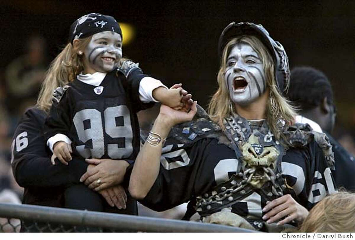 raiders_016_db.jpg Oakland Raiders fans Lynette Grother (face hidden) holds her daughter Nicole Grother (dressed as a skull girl), 3, both of Lakewood, as Kathy Sandelin (Nicole's aunt) (dressed as a skull lady), of Sonora, cheers for the Raiders vs. the Kansas City Chiefs at McAfee Stadium. Event on 9/18/05 in Oakland. Darryl Bush / The Chronicle MANDATORY CREDIT FOR PHOTOG AND SF CHRONICLE/NO SALES-MAGS OUT