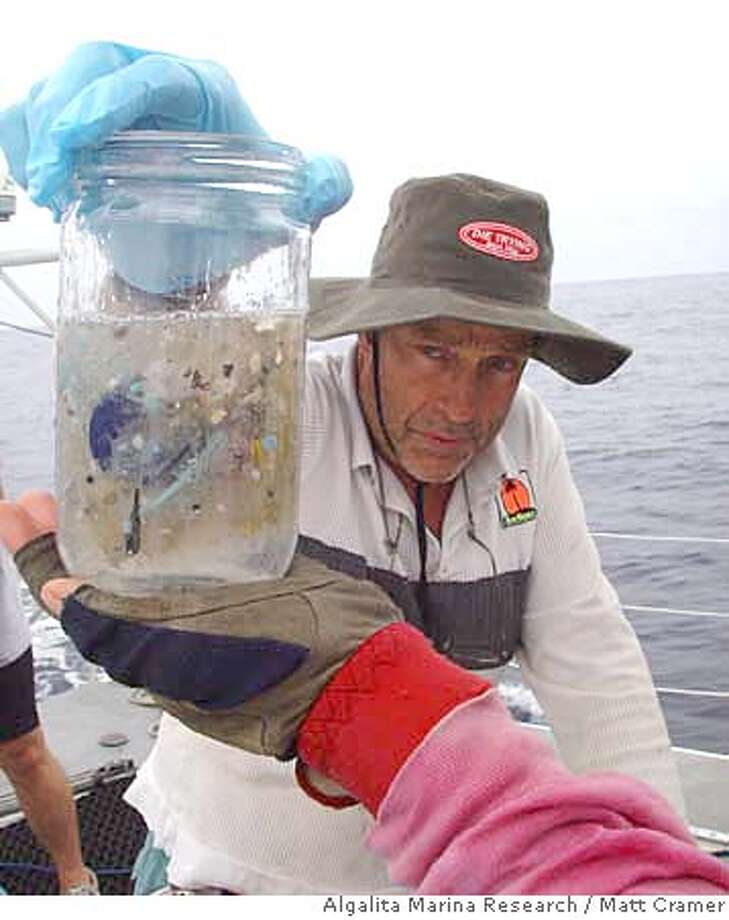 oceantrash30_ph.JPG This picture shows marine researcher Charles Moore on an expedition in the Pacific Ocean sometime between July through September of 2002. He holds a sample of ocean water from the North Central Pacific Gyre that contains small pieces of plastic. Moore, who works at the Long Beach-based Algalita Marina Research Foundation, has been studying the stew of plastic and marine debris floating in the ocean. Matt Cramer / Algalita Marina Research / Courtesy to The Chronicle MANDATORY CREDIT FOR PHOTOG AND SAN FRANCISCO CHRONICLE/NO SALES-MAGS OUT Photo: Matt Cramer / Algalita Marina Re