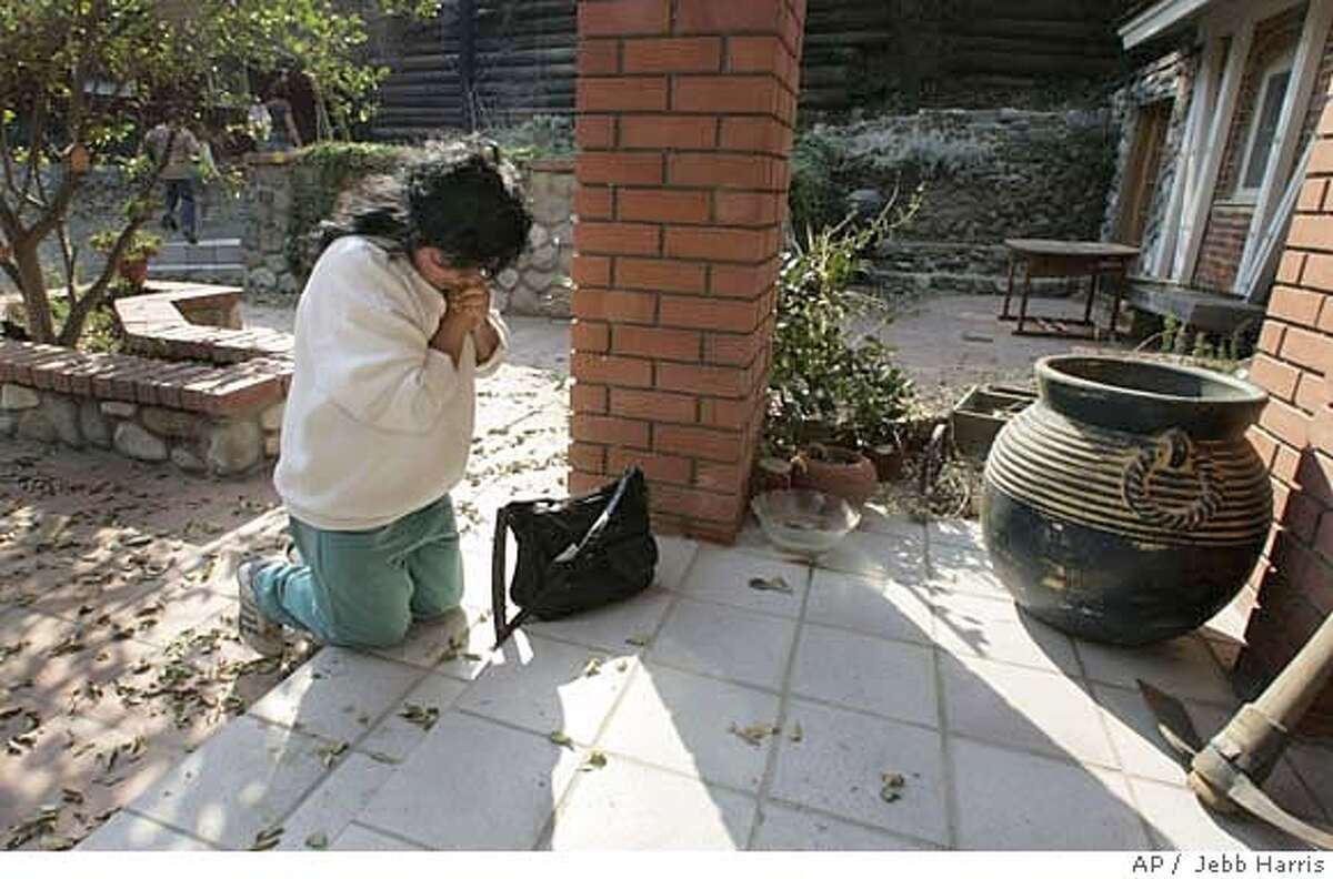 Raquel Prodiz, falls to her knees on Sunday Oct. 28, 2007 on the front step of her house to say a prayer as she and her son arrive to find their Silverado Canyon, Calif. home safe from the wildfires. (AP Photo/The Orange County Register, Jebb Harris) LA TIMES OUT