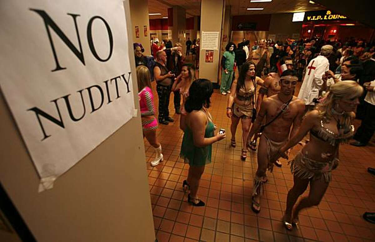 Scantily clothed folks walk past the no nudity sign in the entryway to the 2007 Exotic Erotic Ball at the Cow Palace. Kim Komenich/The Chronicle
