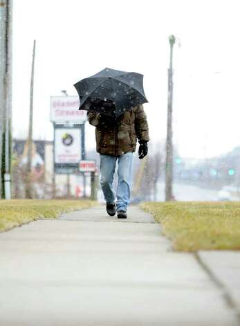 A man shields himself from falling snow Saturday, Feb. 11, 2012 as he walks down Boston Post Road in Milford, Conn. Photo: Autumn Driscoll / Connecticut Post