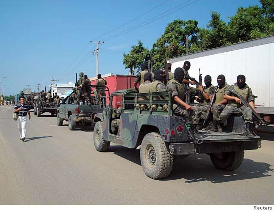 Soldiers stand guard outside a trailer yard in the port of Tampico, northern Mexico, October 5, 2007. Mexican soldiers seized at least 10 tons of cocaine after a gunbattle with drug smugglers at a northern port town on Friday, the army said. The shootout happened during an anti-drugs operation in Tampico in Tamaulipas state, territory of the Gulf Cartel, one of the two most powerful Mexican drug gangs. Picture taken October 5, 2007. REUTERS/Stringer (MEXICO) 0 Photo: STRINGER/MEXICO