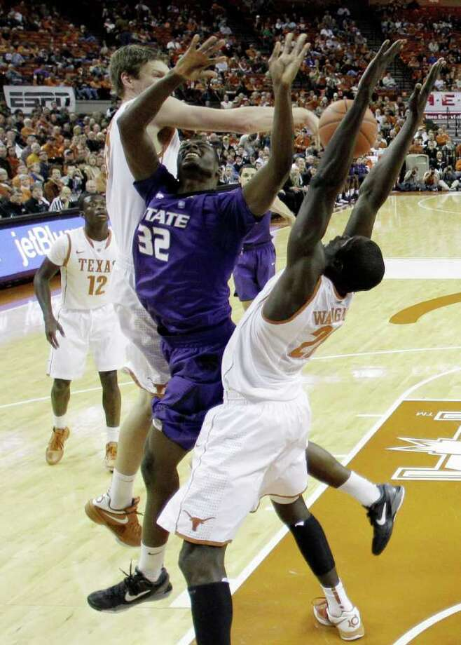 Kansas State Jamar Samuels (32) is blocked by Texas' Clint Chapman, left, as Alexis Wangmene, right, helps defend during the first half of an NCAA college basketball game, Saturday, Feb. 11, 2012, in Austin, Texas. Photo: AP