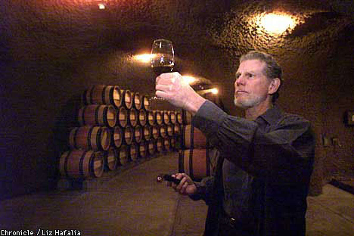 Bill Harlan checked his wine in a cellar dug into a hillside. Chronicle photo by Liz Hafalia