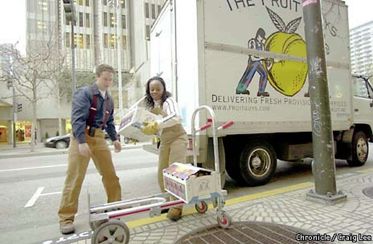 Chris Mittelstaedt, owner of the Fruit Guys, a company that provides fresh fruit to many dot-com businesses, made a delivery with driver Vanessa Nelson. Chronicle photo by Craig Lee