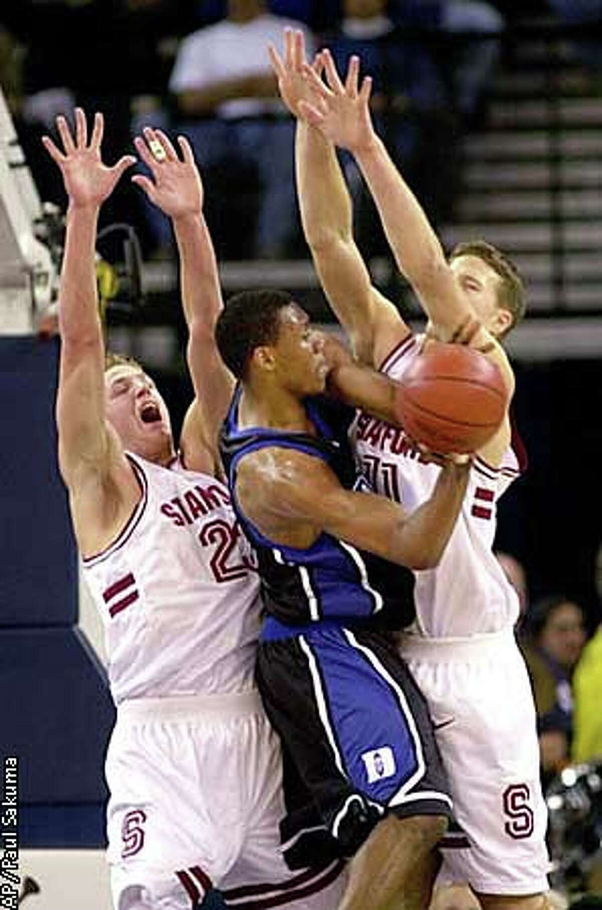 Duke guard Nate James is closely guarded by Stanford forward Casey Jacobsen, left, and center Curtis Borchardt, right, during the first half of the Pete Newell Challenge in Oakland. Associated Press photo by Paul Sakuma