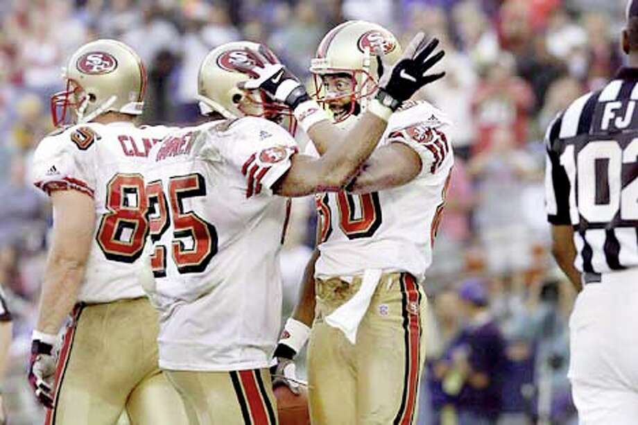 49ers receiver Jerry Rice was congratulated by teammate Charlie Garner (25) after his fourth-quarter TD catch. Chronicle photo by Kat Wade