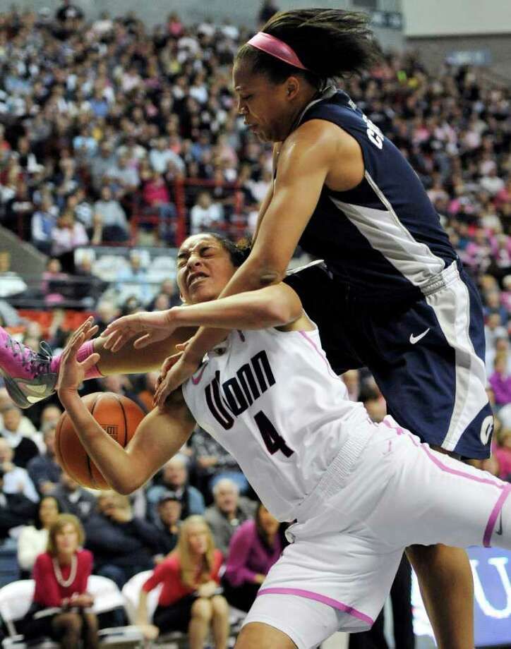 Connecticut's Bria Hartley, bottom is fouled by Georgetown's Adria Crawford, top during the second half of an NCAA college basketball game in Storrs, Conn., Saturday, Feb. 11, 2012. Connecticut won 80-38. (AP Photo/Jessica Hill) Photo: Jessica Hill, Associated Press / AP2012