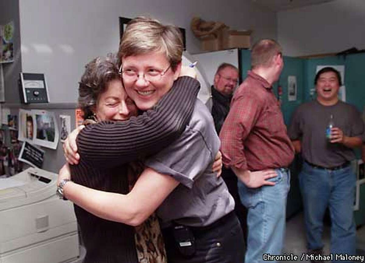 Examiner photographer Katy Raddatz (left) got a hug from Director of Photography Liz Mangelsdorf, who was honored with chocolates from her staff. Chronicle photo by Michael Maloney
