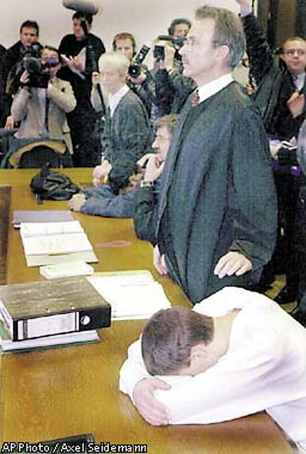 Two of three American teens, covering their faces on the tables, sat beside their lawyers, Bernd Kroner,  (right, standing) and Ulrich Endres, (hand on chin) in the Darmstadt, Germany state court before hearing their sentence. The American teenagers were convicted Friday of murder for dropping stones from an overpass onto passing cars, which  killed two women and injured four other motorists. Associated Press photo by Axel Seidemann