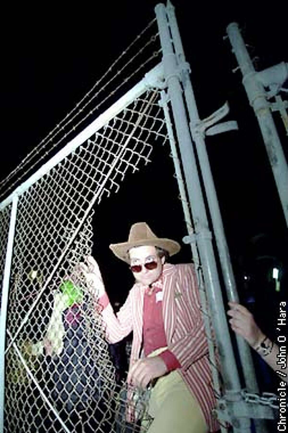 Paul deJong climbs through a fence near McCovey Cove, where Popcorn Anti-Theater audience members play a 20-minute game of Zombie Tag. Chronicle photo by John O'Hara