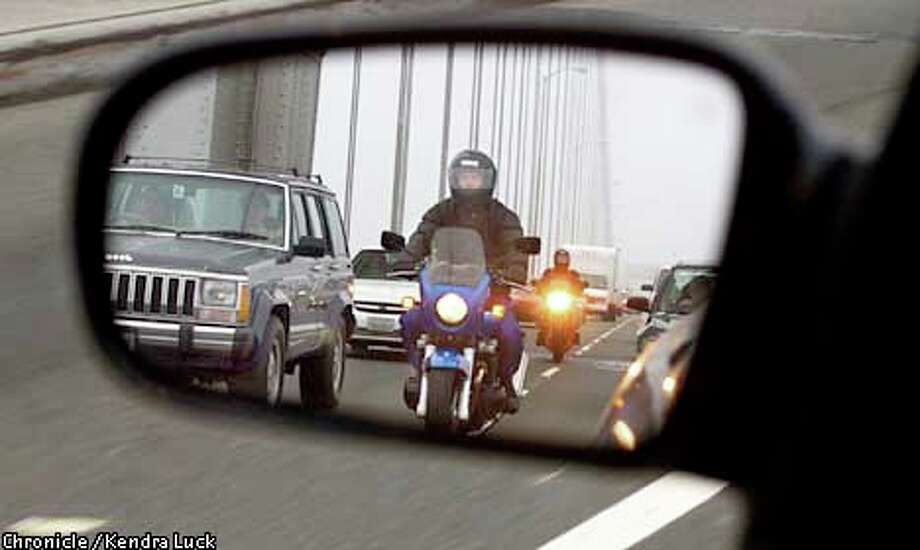 Motorcyclists made their way through morning commute traffic on the upper deck of the Bay Bridge by squeezing between lanes of cars. Chronicle photo by Kendra Luck