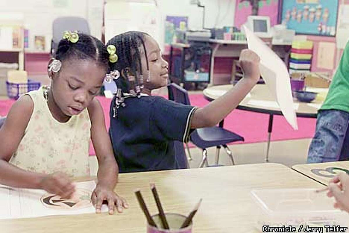 Ta'Leah Williams worked on a writing exercise while Destiny Smith proudly showed off her work to the teacher. Chronicle photo by Jerry Telfer