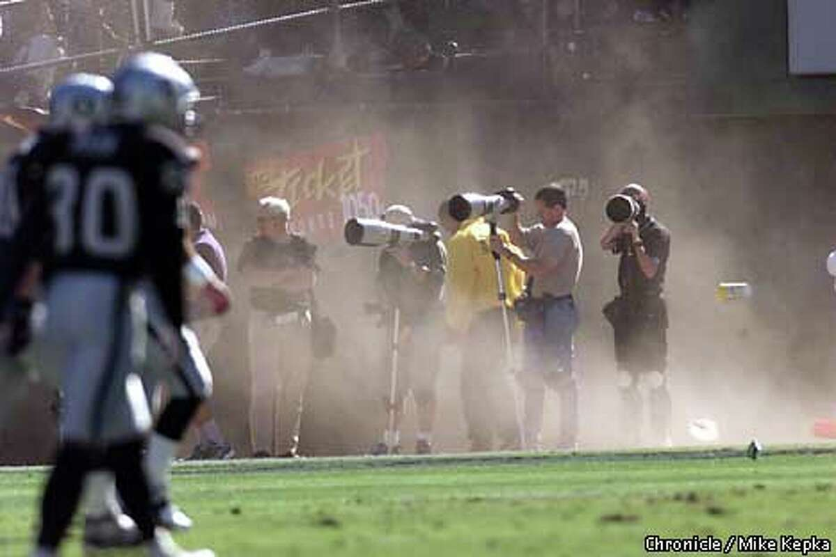Wind gusts kicked up dust along the sideline as photographers attempted to focus through the blurry images. Chronicle photo by Mike Kepka