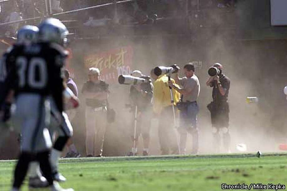 Wind gusts kicked up dust along the sideline as photographers attempted to focus through the blurry images. Chronicle photo by Mike Kepka / CHRONICLE