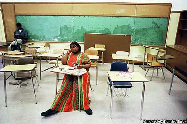Cherice Nunn, who looked through some books she found in a classroom cabinet, and Ferris Patrick were two of the three students who showed up on the last day of Ernest Bagner's class. Cherice passed and will begin high school. Chronicle photo by Kendra Luck