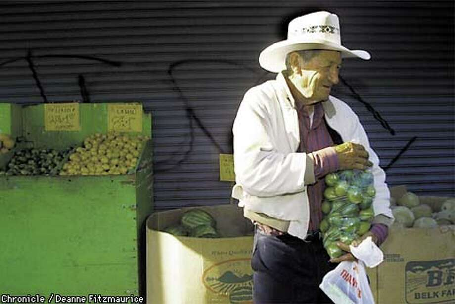 Gabriel Hueso buys a bag of limoncitas (sweet Mexican limes) at Casa Lucas Market. Chronicle photo by Deanne Fitzmaurice