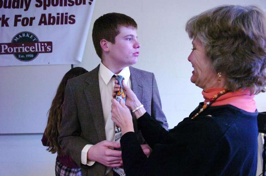 Lynn Erezzini adjusts her son Karl's tie before he plays cello and sings as  Abilis hosts an open house to kick off the sale of its inaugural notecard and jewelry collections at the Greenwich headquarters, 50 Glenville St Sunday afternoon, Sept. 8, 2009. Erezzini, 18, who is austistic, sang songs including Bella Notte, Edelweiss and Zip-a-Dee-Doo-Dah to the delight of the guests at Abilis. Photo: Keelin Daly / Greenwich Time