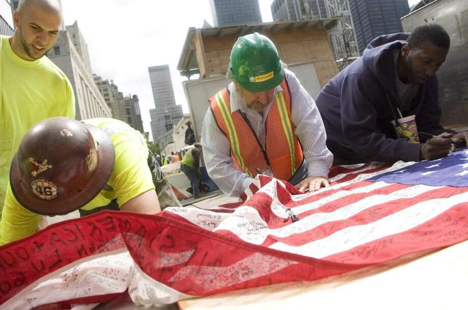 John Mallozzi, of Stamford, a member of the board of representatives, is a structural engineer working at the Freedom Tower site in New York. He signs an American flag at the site on Thursday, Sept. 10, 2009. Photo: Chris Preovolos / Stamford Advocate
